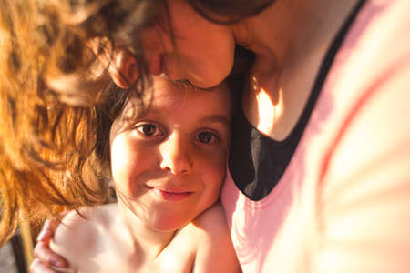 Portrait of a child hugging a mother, a boy spends time with mom, a woman gently hugs her son. Cute boy looks at his beloved mother. Sunset light passing through the hair.