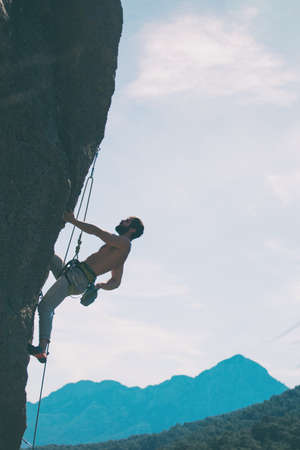 A rock climber climbs a rock against the background of mountains and sky, a man trains strength and endurance, overcoming the fear of heights, training in nature.