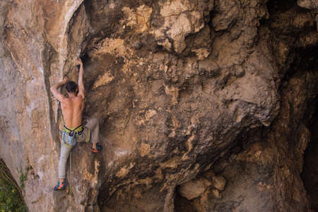 A strong climber climbs a rock, a man trains strength and endurance, overcoming the fear of heights, training in nature, rock climbing in Turkey.