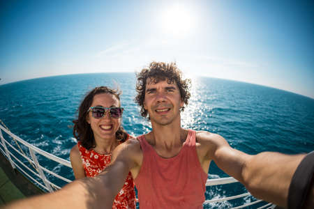 The family is sailing on a cruise ship, a girl with husband are standing at the fence on the ship and looking at the sea, traveling by ferry, a man with girlfriend take selfies on the ocean. Archivio Fotografico