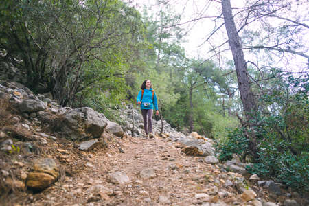 A girl with a backpack walks along a forest trail, sights of Turkey, travel through picturesque places, trekking, hiking, a woman walks along a tourist route, mountain road.