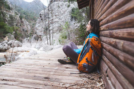 A woman with a backpack sits on the porch of an old wooden house. The traveler found a hut for an overnight stay. Shelter for the traveler. Traveling alone through scenic spots. Pensive girl.