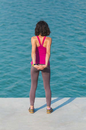 Woman warming up before jogging. The girl is stretched on the city promenade. Training in the city. Brunette doing sports exercises on a background of water. Stretching. Workout. Archivio Fotografico