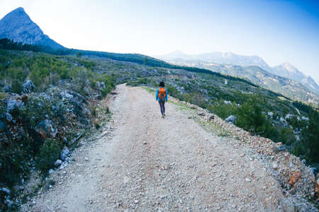 A woman with a backpack is walking along a mountain road, Girl on a background of beautiful mountains, Traveling to scenic spots, Hiking alone. Archivio Fotografico