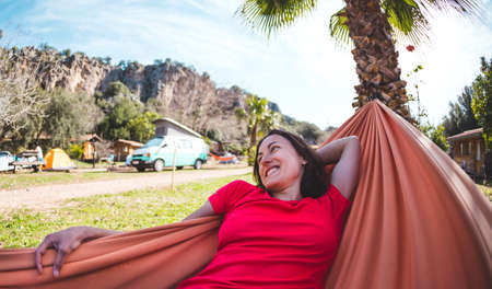 A smiling woman is lying in a hammock, The girl is resting in nature, Camping, Holidays in Turkey, The brunette lies in a hammock on a background of palm trees.