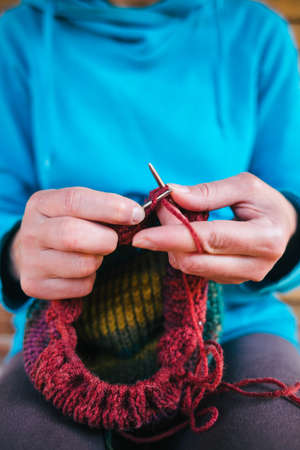 Woman knits a hat from woolen yarn. Female hands close-up. Handmade. Colored yarn and knitting needles. Archivio Fotografico
