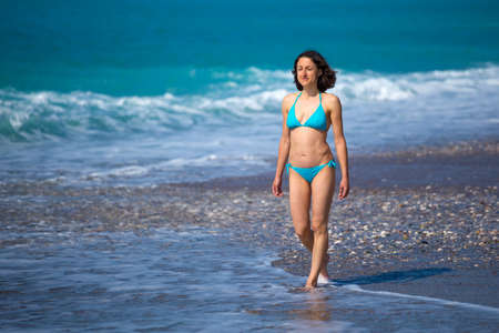 A woman in a swimsuit is walking along the sea waves, Turkish girl on the beach of Antalya, A brunette is walking along the beach, Holidays in Turkey.