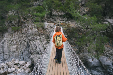 A girl with a backpack walks on a suspension bridge, sights of Turkey, travel through scenic places, trekking, hiking, a woman walks along a tourist route, mountain road, canyon.