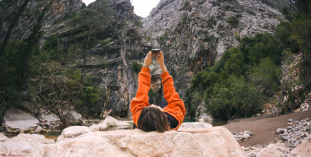 A woman lies on a large stone and takes a selfie on a smartphone, A girl is photographed against a background of beautiful rocky mountains, Traveling to scenic spots.