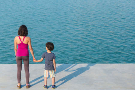 A boy with his mother stand on the promenade and look at the water. A woman walking with her son on a city street. A young mother holds her baby's hand. Archivio Fotografico