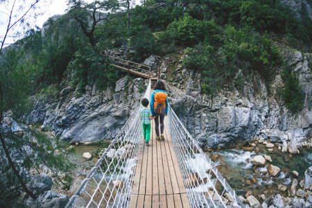 A woman travels with a child through picturesque places. A girl with a backpack crosses the canyon on a suspension bridge. A boy walks along a mountain trail with his mother. Walk through the woods.