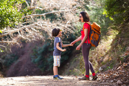 A woman walks with her son through the forest, The boy with his mother go hiking, A child with a backpack is in the park, Travel with children, The kid holds mom's hand, Mountain trail, Mothers Day. Archivio Fotografico