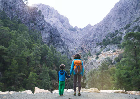 A woman and a child look at the grand canyon and mountains, a trip with children, a boy with a mother on a hike, a girl with a backpack, Mountain trail. Archivio Fotografico