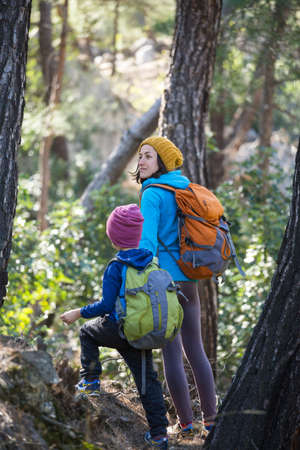 A woman walks with her son through the forest. The boy with his mother go hiking. A child with a backpack is in the park. Travel with children. The kid holds mom's hand. Mountain trail. Archivio Fotografico