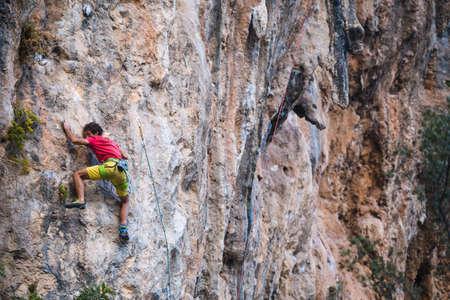 A strong man climbs a cliff. Climber overcomes a difficult climbing route on a natural terrain. Rock climbing in Turkey. Beautiful orange rock.