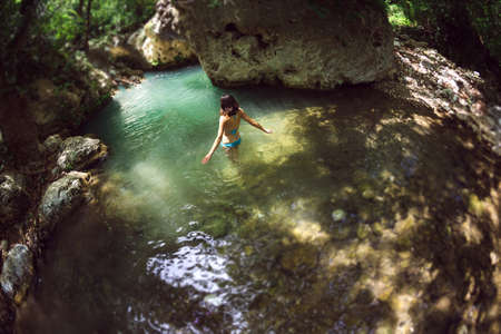 A woman in a swimsuit swims in a mountain river, The girl goes into cold water, Picturesque place of Turkey. Archivio Fotografico