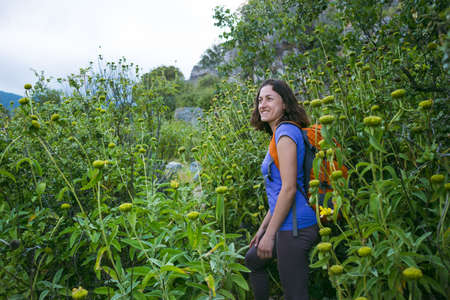 A woman with a backpack goes along the path through the tall grass, a girl on a walk in nature after quarantine, outdoor activities.