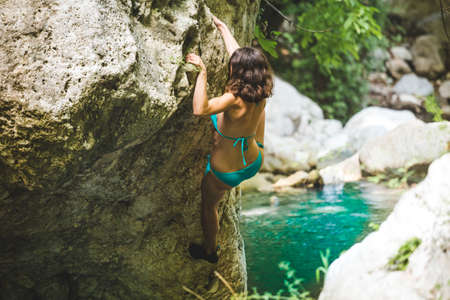 A woman in a swimsuit climbs a cliff above the water, Climbing over a mountain river, Bouldering in Turkey, A strong climber is training on a natural terrain, Deep water solo.