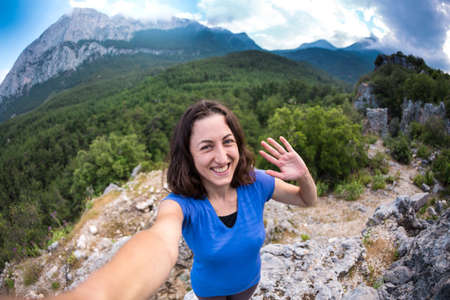 A woman takes a selfie on top of a mountain, a girl is photographed against a background of a mountain valley, a trip to the picturesque places of Turkey. Archivio Fotografico
