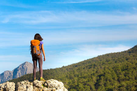 A woman with a backpack stands on top of a mountain and admires the beauty of a mountain valley, The girl travels to beautiful places, Reaching the goal. Beautiful landscape. Standard-Bild