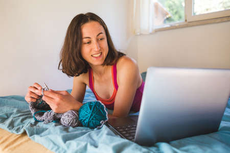 A woman is engaged in knitting, knitting for sale, learning to knit online, a girl watching needlework lessons, a laptop and home hobbies.