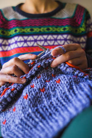 A woman knits from thick yarn. Handmade clothes. The girl sits on the couch and goes in for her hobbies. Knitting close up.