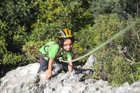 The child is climbing on a natural terrain. A boy in helmet climbs a rock on a background of mountains. Extreme hobby. Athletic kid trains to be strong. Rock climbing safety.