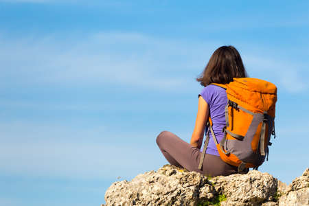 A woman with a backpack sits on top of a mountain and admires the beauty of a mountain valley. The girl travels to beautiful places. Reaching the goal. Beautiful landscape.