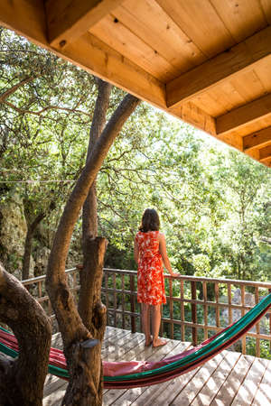 A woman in a red dress stands on the terrace of a wooden house and enjoys the view, Veranda in the shade of trees, Balcony with garden view.