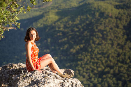 A girl in a red dress on a large rock on top of a mountain against the backdrop of a mountain valley, a trip to the picturesque places of Turkey.