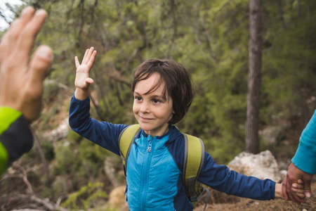 A boy with a backpack walks through the forest with his parents, a child holds out his palm to give five, a trip with children, a boy gives his hand to dad.