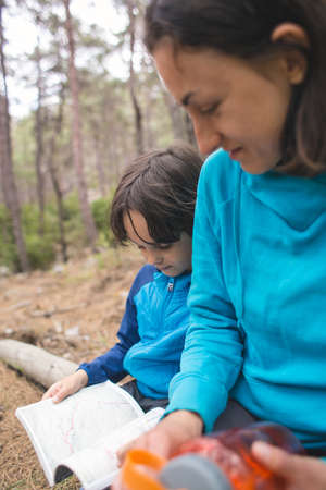 A child and his mother are exploring the forest, a boy is looking for a location on a map, a woman is teaching her son to use the map, a hike in the mountains with children.