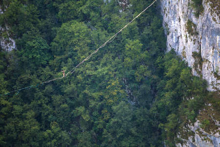 Highline in the mountains. A man goes on a stretched sling. Highline is on the line. A tightrope walker catches balance. Equilibrium. Confidence in a tense situation. Stock Photo