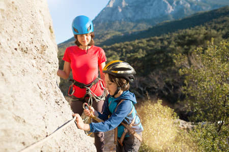 Mother teaches a child how to use safety equipment. A boy in a helmet goes through Via Ferrata. A woman instructs how to use a carabiner for belaying. Mountain tourism and mountaineering for children. Banque d'images