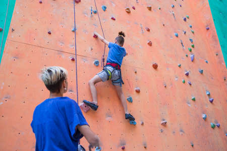 A coach teaches a child, a woman is belaying her son, a boy and his mother train together, children's training climbing, a boy climbs the wall, climbing gym Standard-Bild