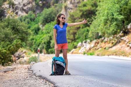 A girl with a backpack travels hitchhiking, a woman stands on a mountain road and catches a car, Brunette is waiting for transport, Hitchhiking in Turkey. Standard-Bild