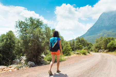 A woman with a backpack is walking along a mountain road, Girl on a background of beautiful mountains, Traveling to scenic spots, Hiking alone. Standard-Bild