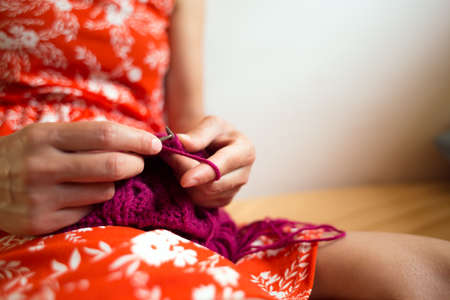 Woman knits while sitting on the bed, Women's hands knit a hat, The girl is engaged in creativity during quarantine, Handmade, Favorite home hobby.