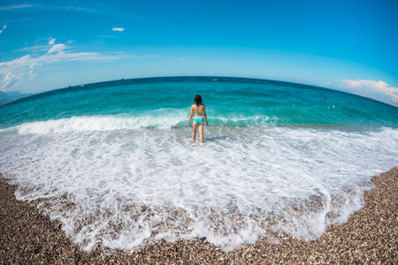 A girl in a swimsuit walks along the beach and looks at the sea, sea waves and the blue sky, a woman sunbathes on the beach, rest on the ocean coast.