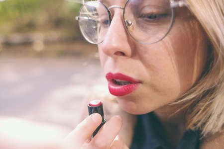 Woman paints her lips with red lipstick. Girl puts makeup on the street. Portrait of the blonde in glasses.