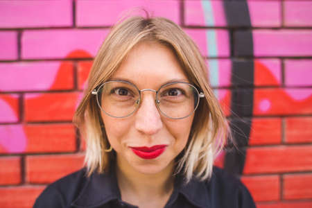 Portrait of a blonde in glasses on a brick wall background. A woman walks around the city. The smiling girl. Lips with red lipstick.