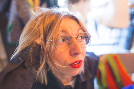 Portrait of a blonde in glasses. The smiling girl. Lips with red lipstick. A woman is sitting in a cafe.