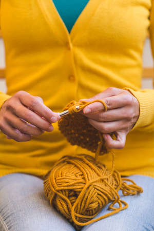 Woman crochets. Female hands close-up. The girl is engaged in needlework. A ball of yellow thread and a crochet hook.