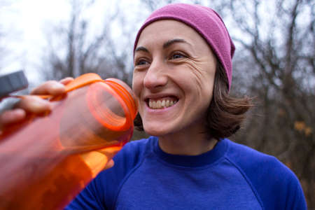 The girl runs through the autumn forest. A woman is training in nature. Runner is preparing for the marathon. Endurance. Girl drinks water after jogging. Sportswear for jogging in the cold season. Standard-Bild