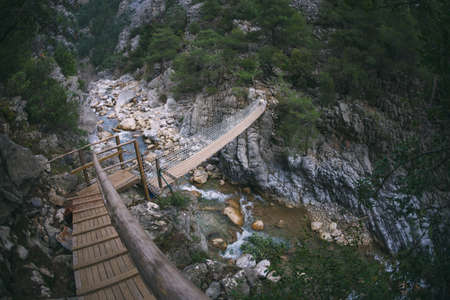 A mountain river at the bottom of the canyon, a rapid stream, large stones on the river bank, the picturesque nature of Turkey, a suspension bridge across the river.