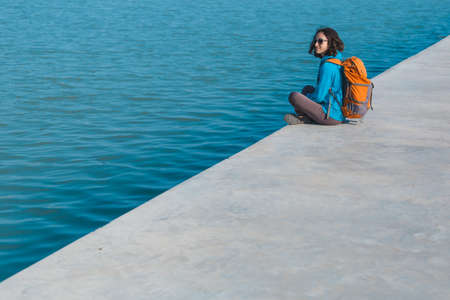 A woman with a backpack sits on the river bank, a girl looks at the water, a walk along the city embankment, the sea coast.