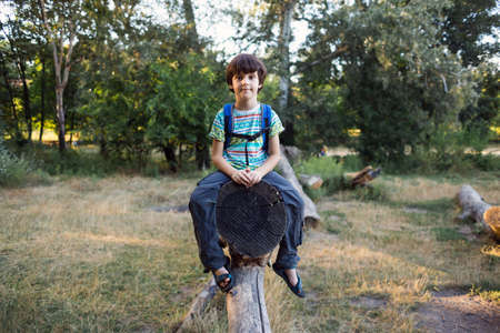 A boy with a backpack sits on the trunk of a fallen tree, a child walks through the forest, a kid is exploring nature. Archivio Fotografico