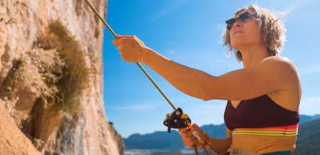 the girl insures her partner while climbing the mountains. rock climbing safety and insurance concept. healthy lifestyle and sports in nature on a sunny day. Stock fotó