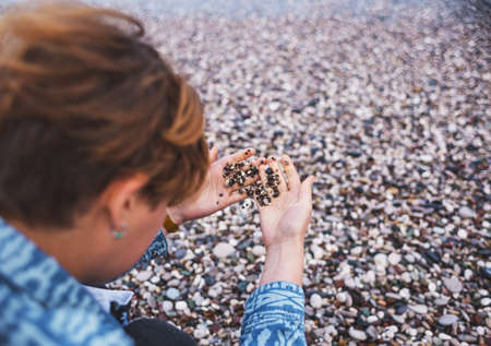 A girl with short hair sits on the beach and touches pebbles, a red-haired girl holds small pebbles on her palm