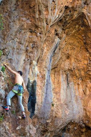 A  man climbs a cliff.